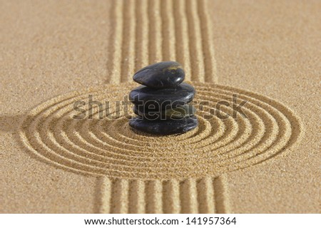 Japanese garden with stacked stones in raked sand - stock photo