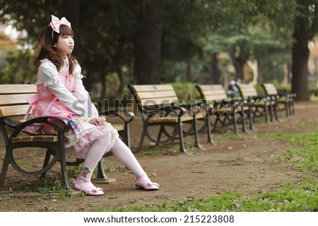 Japanese girl in lolita cosplay fashion sitting on a bench, Tokyo - stock photo