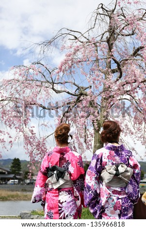 Japanese girl in traditional dress called Kimono with Sakura blossom - stock photo