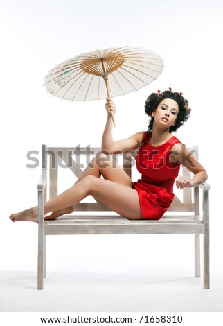 Japanese girl is sitting on a bench with an umbrella - stock photo