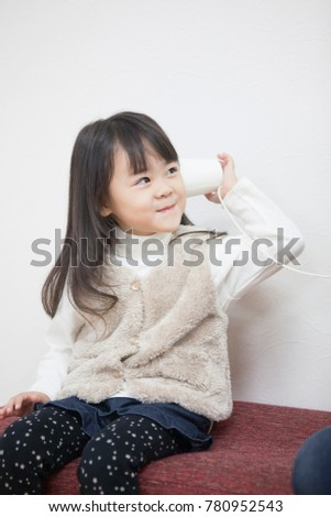 Japanese girl playing with a paper cup phone