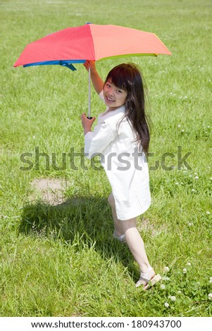 Japanese girl smiling with parasols in grassland