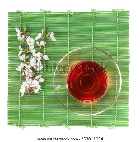 Japanese green tea and sakura branch over bamboo mat. Isolated on white background  - stock photo