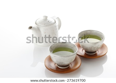 Japanese green tea in porcelain cup and tea pot. - stock photo