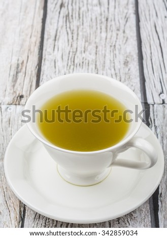 Japanese green tea in white cup over wooden background - stock photo