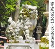 Japanese guardian lion statue infront of a shrine - stock photo