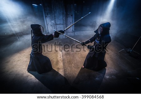 Japanese kendo fighters with bamboo swords competing in dark industrial building. - stock photo