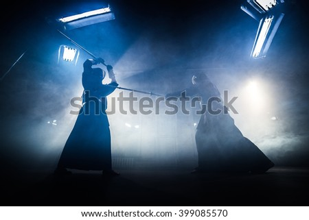 Japanese kendo fighters with bamboo swords competing in dark industrial building.