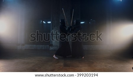 Japanese kendo fighters with bamboo swords competing in dark industrial building in the fog. - stock photo