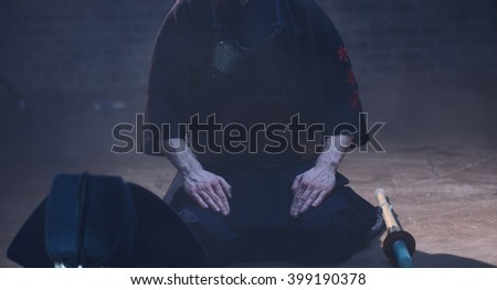 """Japanese Kendo. The fighter sits in Kendo armor in the fog. (the inscription in Japanese """"Shogun"""") - stock photo"""