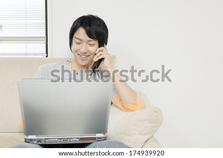 Japanese Man having a conversation on the mobile phone while looking at the computer - stock photo