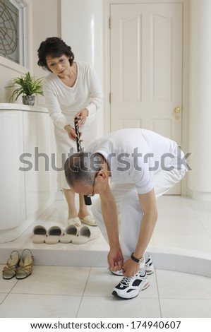 Japanese man tying his shoes in the house