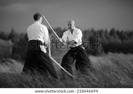 Japanese martial arts practitioners outside, monochrome - stock photo