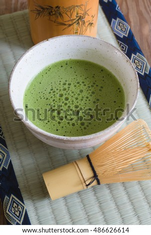 Japanese Matcha green tea in a chawan or traditional ceramic bowl with a tatami mat background