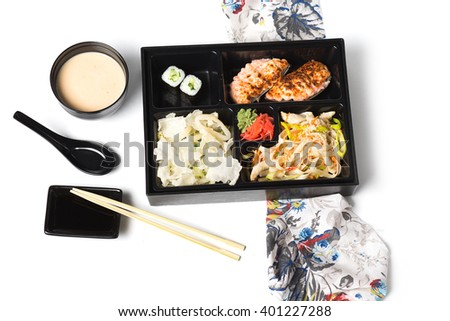 Japanese Meal in a Box Bento isolated on white background - baked salmon with rice, salad with chicken, sushi and rolls - stock photo