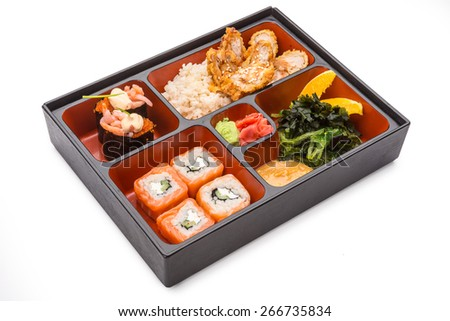 Japanese Meal in a Box (Bento) isolated on white background - shrimp, salad, baked chicken with rice, oranges, sushi and rolls - stock photo