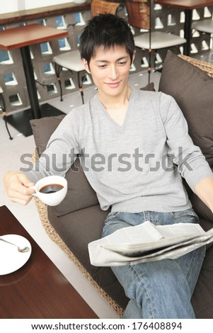 Japanese men reading a newspaper with a cup of coffee
