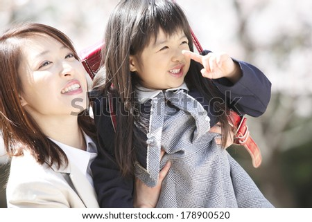 Japanese mother and elementary girls who look up at the cherry tree