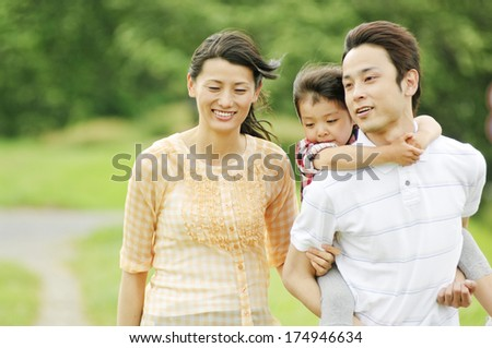 Japanese Mother walking beside a father giving piggyback ride to daughter - stock photo