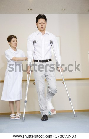 Japanese Nurse walking together with a patient with crutches
