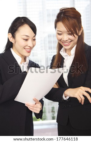 Japanese Office Lady in conversation while looking at the material - stock photo