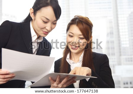 Japanese Office Lady in the meeting while watching the material - stock photo