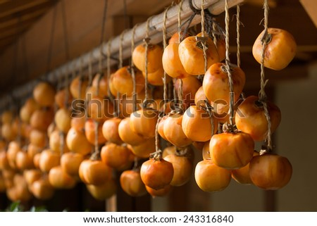 Japanese peeled persimmons being dried in the sun  - stock photo