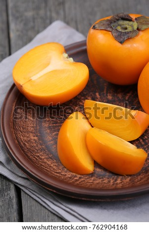 Japanese persimmons in ceramic plate on wooden table
