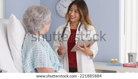 Japanese physician speaking with elderly patient in hospital bed - stock photo
