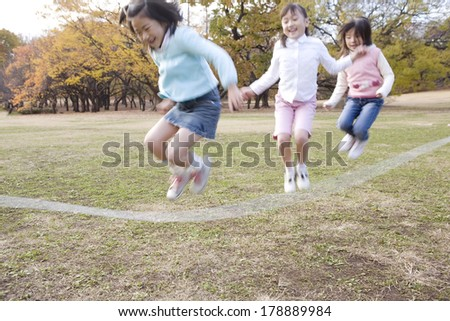 Japanese Primary students jumping the long rope together - stock photo