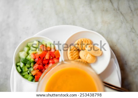 Japanese pumpkin orange soup served in bowl on table with salad and bread - seen from above - stock photo