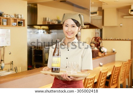 Japanese restaurant clerk carries the beer