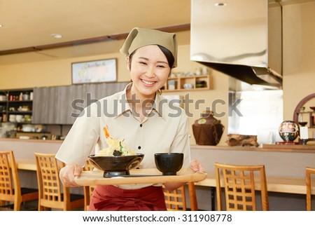 Japanese restaurant clerk carries the set lunch - stock photo