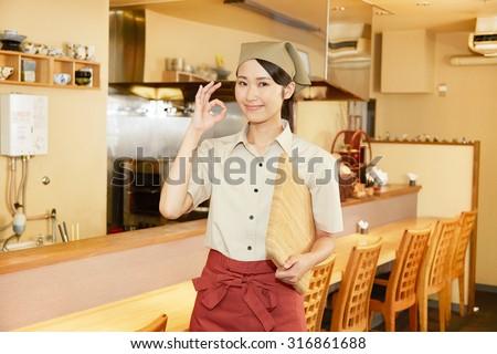 Japanese restaurant clerk OK pose gesture - stock photo