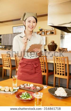 Japanese restaurant clerk taking an order - stock photo