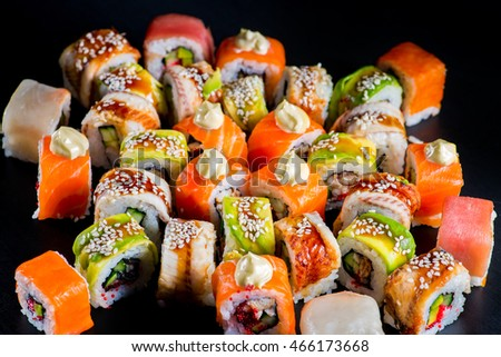 Japanese rolls with fish on a black background