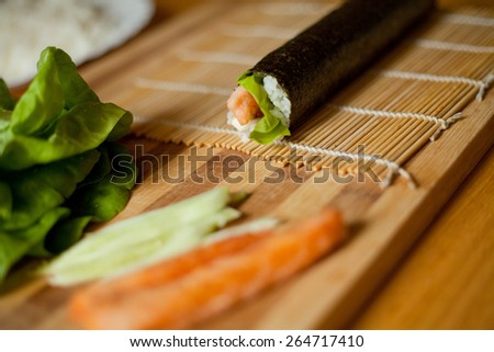 Japanese salmon sushi home preparation in steps - rolling. - stock photo
