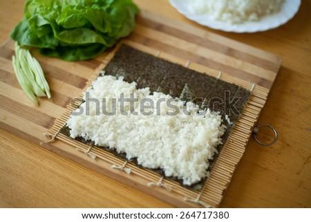Japanese salmon sushi preparation  -  rice on nori and mat. - stock photo
