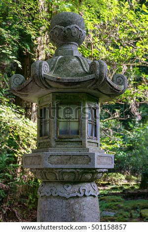 Japanese stone lantern, spirit house surrounded by trees with lush green leaves
