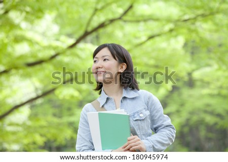 Japanese student smiling surrounded by nature,