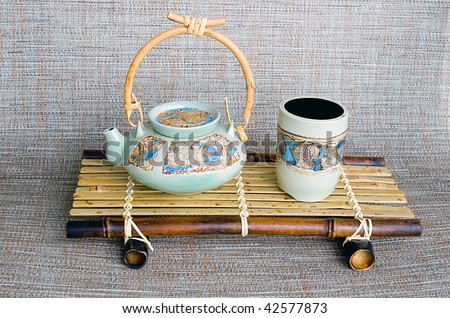 Japanese style ceramic teapot and cup on the bamboo stand