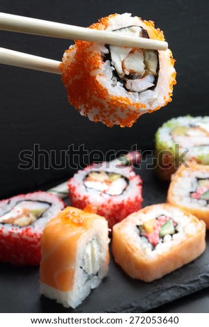 Japanese sushi and rolls on a dark background - stock photo
