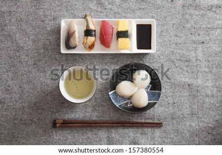 Japanese Sushi and Sashimi -- Egg, Tuna, Eel, Swordfish, Scallop, Green tea - stock photo