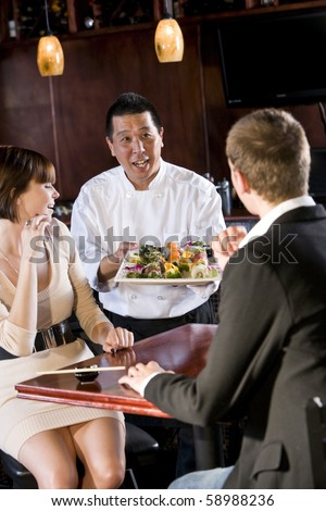 Japanese sushi chef serving platter of sushi to young couple - stock photo