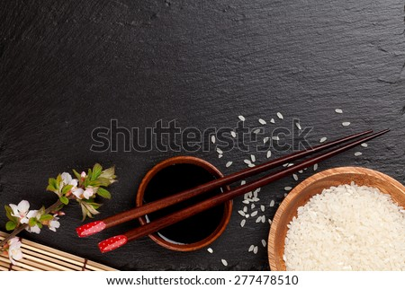Japanese sushi chopsticks over soy sauce bowl, rice and sakura blossom on black stone background. Top view with copy space - stock photo