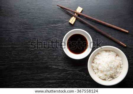 Japanese sushi chopsticks over soy sauce bowl, rice on black background. Top view with copy space - stock photo