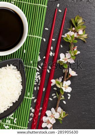 Japanese sushi chopsticks, soy sauce bowl, rice and sakura blossom on black stone background - stock photo