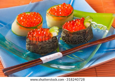 Japanese sushi ikura maki rolls of caviar, rice, dried nori seaweed and cucumber on a transparent glass plate on a blue ceramic platter on orange background horizontal - stock photo