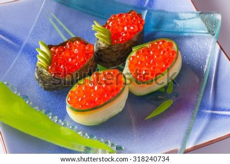 Japanese sushi ikura maki rolls of caviar, rice, dried nori seaweed and cucumber on a transparent glass plate on a blue ceramic platter horizontal - stock photo