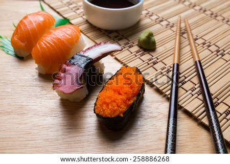 Japanese sushi on wood cut board and mat with chopsticks, wasabi and soy sauce - stock photo